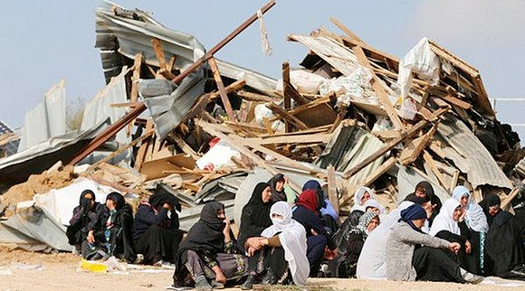Women sit next to the ruins of their dwellings, which were demolished by Israeli bulldozers, in the tiny village of Umm Al-Hiran, in January 2017. Credit: Ammar Awad/Reuterst